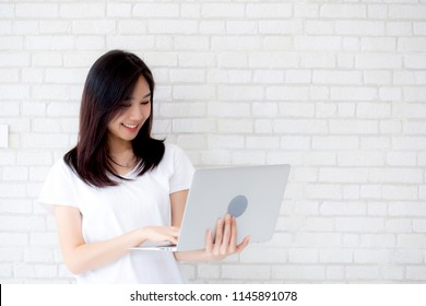 Beautiful of portrait young asian woman smiling and standing holding laptop on brick cement wall background, girl working computer, business and lifestyle concept.