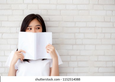 beautiful portrait young asian woman happy hiding behind open the book with cement or concrete background, girl standing reading for learning, education and knowledge concept.