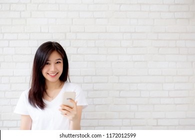 Beautiful of portrait young asian woman touch phone and smile standing on cement brick background, freelance female calling telephone, communication concept.