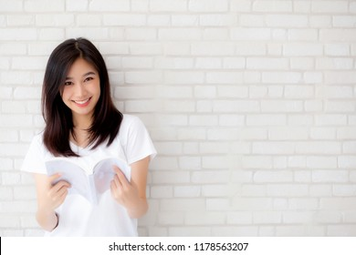 Beautiful of portrait young asian woman happiness relax standing reading book on concrete cement white background at home, girl happy study content literature, education and lifestyle concept.