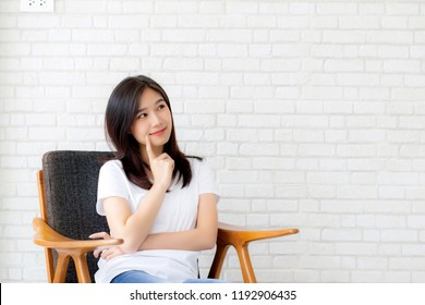Beautiful portrait young asian woman confident thinking with cement and concrete background, girl sitting on chair expression serious or doubts with idea, lifestyle concept.