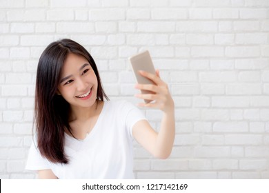 Beautiful portrait young asian woman taking a selfie with smart mobile phone on concrete cement white background, girl is photographing with happy and smile with fun, lifestyle concept.