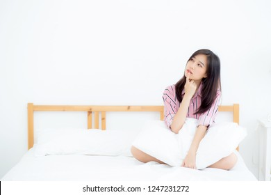Beautiful portrait young asian woman smile confident thinking while wake up in the bedroom, girl sitting expression serious or doubts with idea, lifestyle and relax concept.