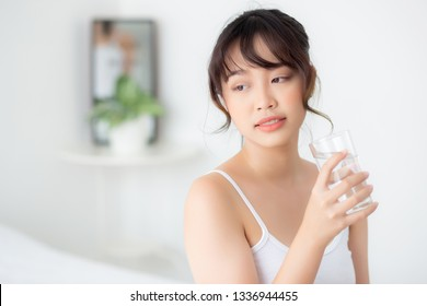 Beautiful portrait young asian woman smile and drinking water glass with fresh and pure for diet, beauty girl thirsty and charming holding beverage with healthy in the bedroom, health care concept.
