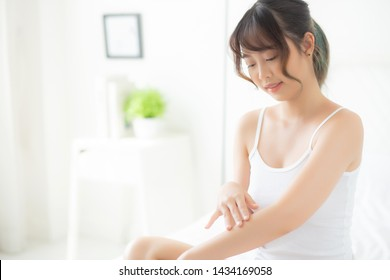 Beautiful portrait young asian woman smile applying sunscreen cream or lotion on skin care at bedroom, beauty asia girl using makeup and cosmetic for smooth and silky, wellness and health concept.