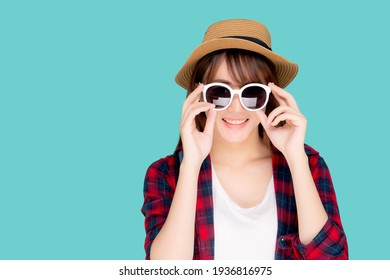 Beautiful portrait young asian woman wear hat and holding sunglasses smiling confident enjoy journey summer trip in vacation isolated on blue background, tourist asia girl cheerful with travel.
