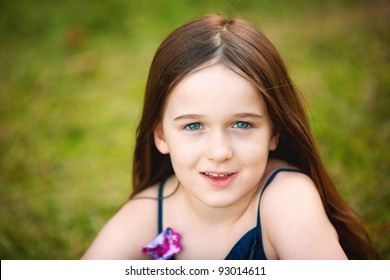 A beautiful portrait of a young brunette six year old in the outdoors