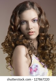 beautiful portrait of young pretty brunette with long curly hair and spring dress
