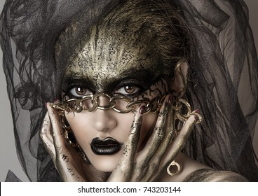 Beautiful portrait of a young sexy sorceress with black and gold face art with gold chain. Halloween make up. Big sexy black lips