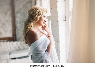 Beautiful portrait of young woman at morning with flowers near window. Wedding dress. Curly hairstyle.