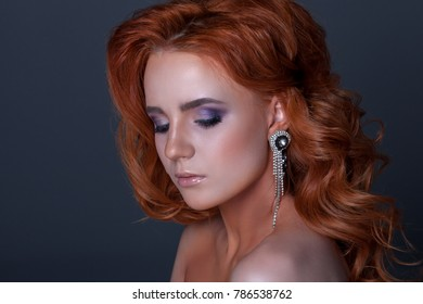 Beautiful portrait of a young woman on a gray background. With creative make-up and a beautiful hairdo. With beautiful earrings.