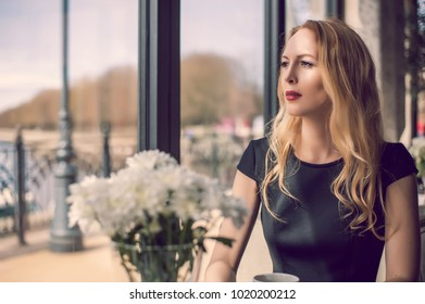 beautiful portrait of young woman sitting in cafe looking at the window on River embankment and waiting boyfriend