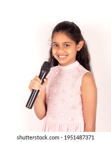 Beautiful portrtait of a confident and smiling indian child holding a mike dressed in pink.