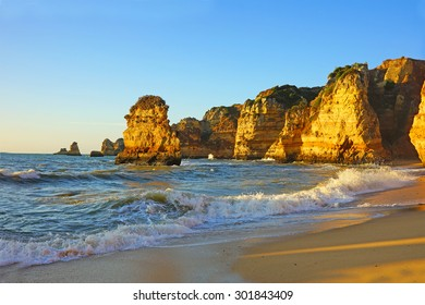The beautiful Portuguese beach at Praia da Dona Ana at sunrise with an incoming tide, sea stacks and rocky cliffs on the coastline of the Atlantic Ocean in Lagos, Algarve, Portugal