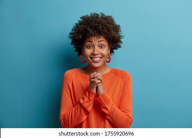Beautiful positive African American woman has imploring look, keeps hands pressed together, hopes for better, wears orange sweater and earrrings, asks for help, pleads for something, poses indoor