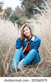 Beautiful positive girl in denim clothes sitting in autumn grass.