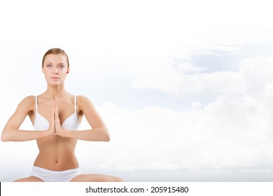 Beautiful positive girl in white underwear sitting on a background of clouds