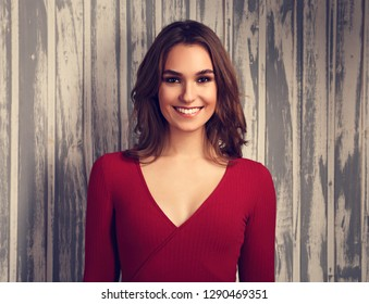 Beautiful positive toothy smiling woman and looking happy in casual red shirt and short curly hair on empty copy space background. Closeup toned portrait