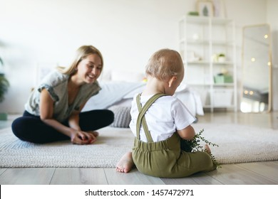 Beautiful positive young European mom sitting cross legged on floor with her infant son, watching him study plant. Blonde mother encouraging baby to do first steps in stylish bedroom interior