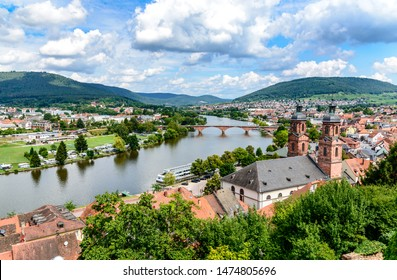 Beautiful postcard View from castle on old german town Miltenberg am Main river, St. Jacob catholic church, main bridge with blue sky and clouds.  Odenwald, Bavaria, Germany