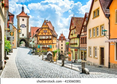 Beautiful postcard view of the famous historic town of Rothenburg ob der Tauber on a sunny day with blue sky and clouds in summer, Franconia, Bavaria, Germany