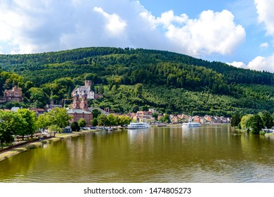 Beautiful postcard View on old german town Miltenberg am Main river, Castle, St. Jacob catholic church, cruise ships, mountain with wood in Odenwald,  Bavaria, Germany