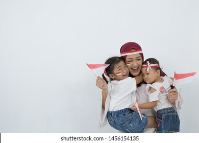 Beautiful Potrait Asian young mother with her daughters celebrating indonesia independence day by raising Indonesian flags
