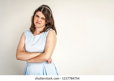 A beautiful pouted and capricious Caucasian brunette girl with crossed hands making unhappy faces. Resentful young woman stock image. Caprice and irritation concept.
