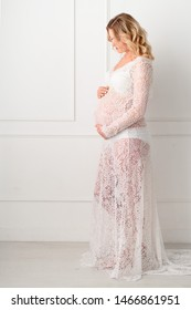 Beautiful Pregant blonde woman holding his belly in light study