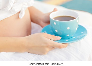 beautiful pregnant belly with a cup in his hand, blue polka dots