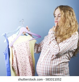 Beautiful pregnant blonde chooses clothes. Portrait of pregnant woman.