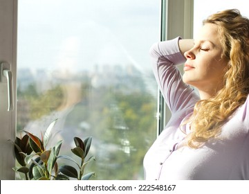 Beautiful pregnant blonde standing near the window and enjoy the sun.