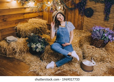 A beautiful pregnant brunette girl in a straw hat and denim overalls is sitting posing in the hay with decorations, a rabbit, flowers and a gerland.