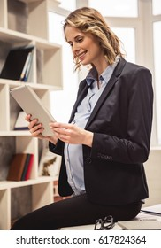 Beautiful pregnant business woman in suit is using a digital tablet and smiling while working in office