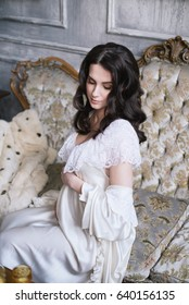Beautiful pregnant girl with black hair sitting on a vintage couch