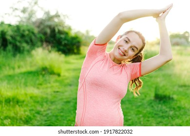 Beautiful pregnant girl is exercising outdoors on the grass. Sports during pregnancy. Healthy pregnancy. Fitness during pregnancy. yoga for pregnant women. Benefits of sports. Healthy life.