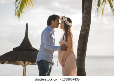 Beautiful pregnant girl and man on the beach
