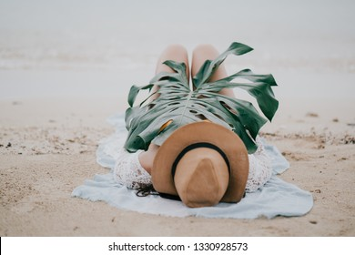 Beautiful pregnant girl  with Yellow bikini and hat sleeping with happiness and relaxing on beautiful tropical beach with green monstera leaf.Blur sea background split color and soft focus.