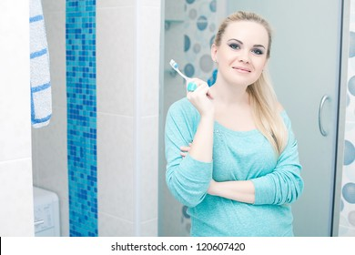 Beautiful pregnant lady holding toothbrush and smiling in her modern bathroom. Indoor shot.