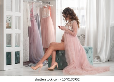 beautiful pregnant lady in a pink dress at home