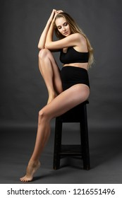 Beautiful pregnant leggy blonde woman wearing black maternity underwear sits on a chair on a gray background and touches her hair. Health, fashion, motherhood. Commercial design. Copy space.