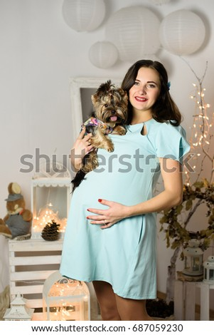 0fd7fe3e113 Beautiful Pregnant Woman with a big belly and little dog on The Christmas