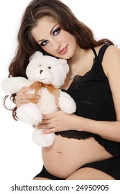 Beautiful pregnant woman in black lingerie holding teddy bear, over white background