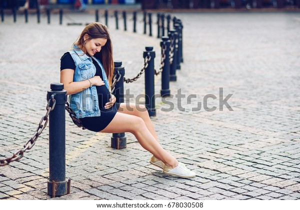 1ec6f7865d715 Beautiful pregnant woman in black tight dress and denim jacket and touching  her belly with love