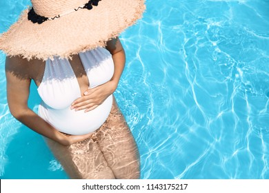 Beautiful pregnant woman in blue swimming pool