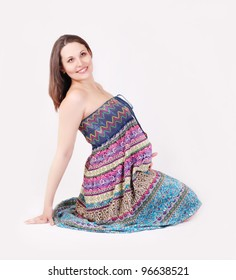 Beautiful pregnant woman in bright summer dress sitting on the floor