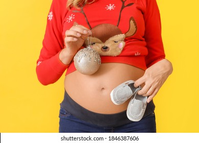 Beautiful pregnant woman with Christmas ball and baby shoes on color background