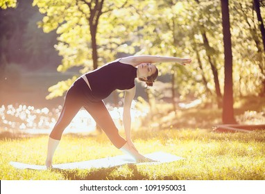Beautiful pregnant woman doing prenatal yoga on nature outdoors. Sport fitness healthy lifestyle while pregnancy. Pregnant woman practicing yoga pose breathing exercise stretching in summer park.