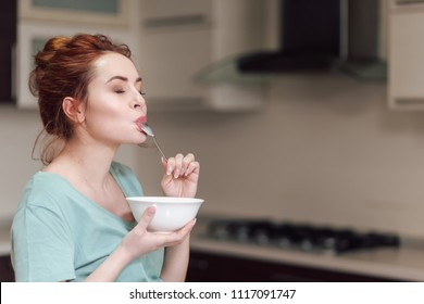 Beautiful pregnant woman eating with lust cereals on breakfast, enjoying meal. Yummy food for pregnant ladies