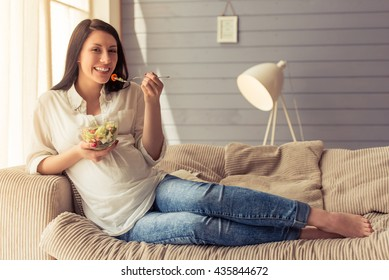 Beautiful pregnant woman is eating salad, looking at camera and smiling while sitting on couch at home